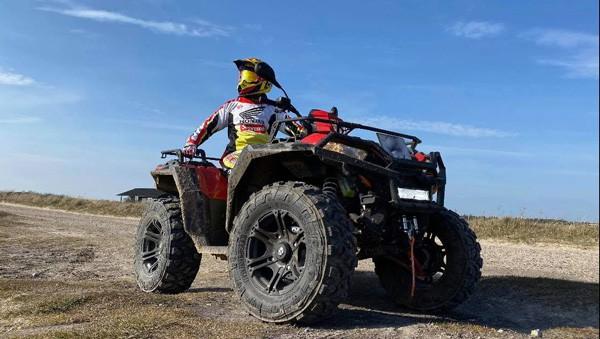 ATV fingregistreret på plader kører på vej med blå himmel i baggrunden