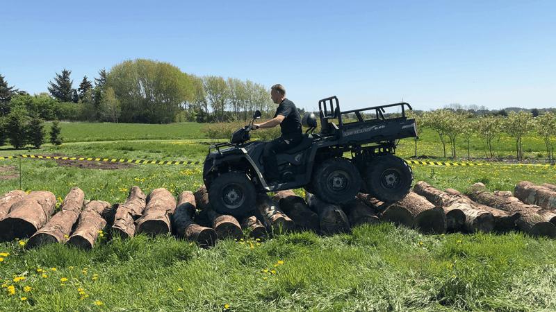 ATV Big boss fra Pilaris kører ubesværet over store træstammer