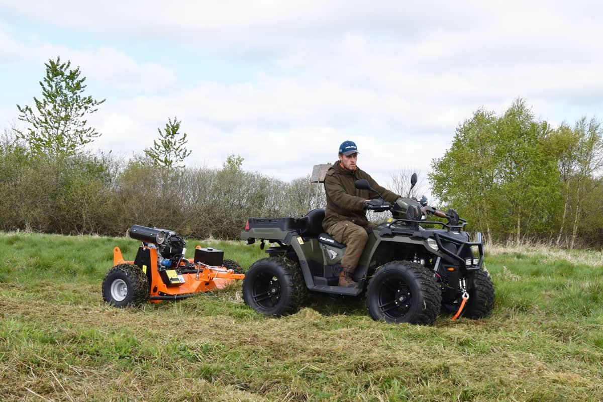 ATV med eftertrukket redskab i groent landskab. Jæger på ATV med slagleklipper.